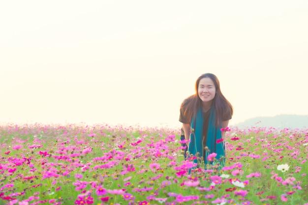 Glückliches asiatisches mädchen im lässigen kleid lächeln und im kosmosblumenfeld im weinlesestilstil stehen.