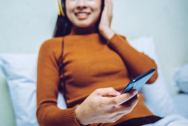 Glückliches asiatisches mädchen mit hehadphones, das musik hört.