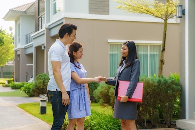 Glückliches asiatisches paar, das ihr neues haus sucht und hände schüttelt