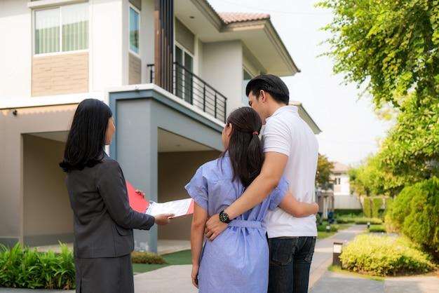 Glückliches asiatisches paar, das ihr neues haus sucht