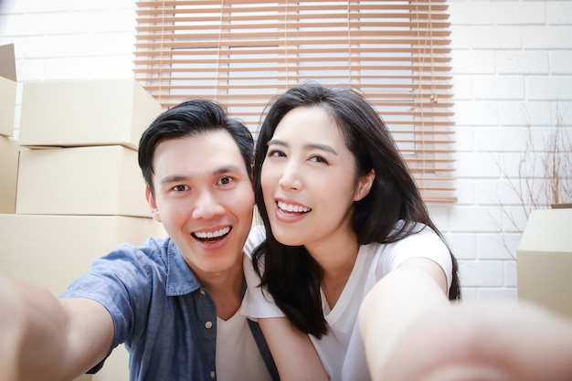 Glückliches asiatisches paar, das in neues zuhause einzieht nehmen sie ein smartphone und machen sie ein selfie.