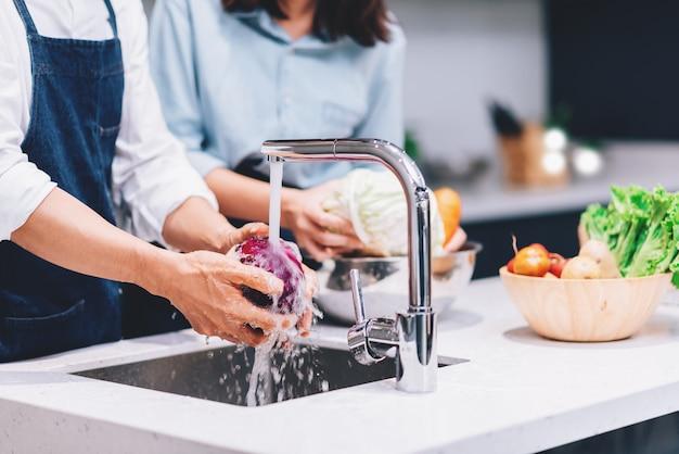 Glückliches asiatisches paar, das zusammen kocht und gemüse in der küche zu hause wäscht. hobby-lebensstil-konzept