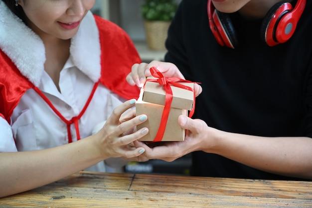Glückliches asiatisches paar, das zusammen öffnende weihnachtsgeschenkbox hält.