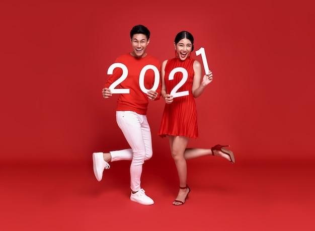 Glückliches asiatisches paar in roter freizeitkleidung mit der nummer 2021, die ein frohes neues jahr mit einem lächeln auf leuchtendem rot begrüßt.