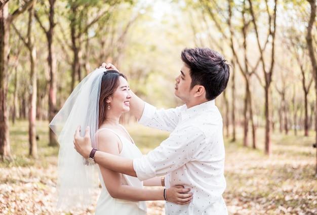 Glückliches asiatisches paar verliebt in baumbogen