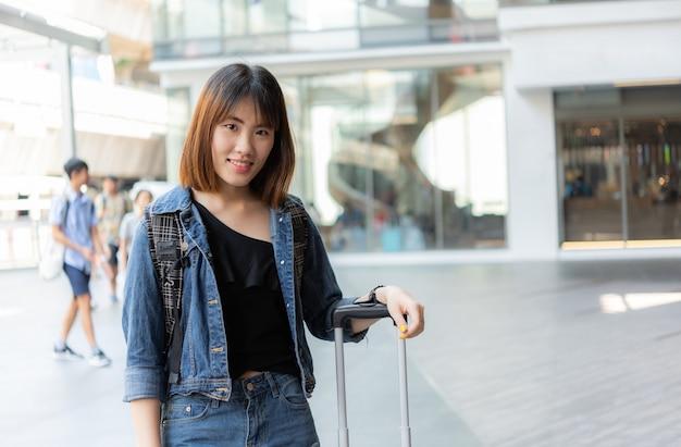 Glückliches asiatisches reisendmädchen mit gepäck in der großstadt