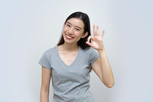 Glückliches asiatisches schönes lächeln der jungen frau mit der okaygeste lokalisiert