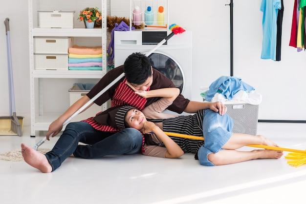 Glückliches asiatisches süßes paar bricht und ruht sich aus, nachdem es zusammen aufgaben erledigt hat. ehemann küsst seine frau, während sie schüchtern ist und versucht, sich zu weigern.