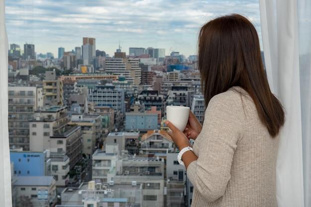 Glückliches asiatisches trinkwasser der jungen frau morgens am fenster des schlafzimmers.