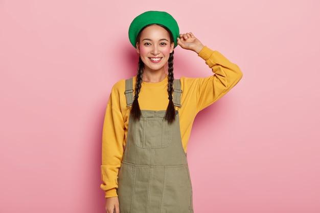 Glückliches asiatisches weibliches modell mit rouge-wangen, hat einen angenehmen gesichtsausdruck, trägt stilvolle baskenmütze, gelbes sweatshirt und denim-sarafan