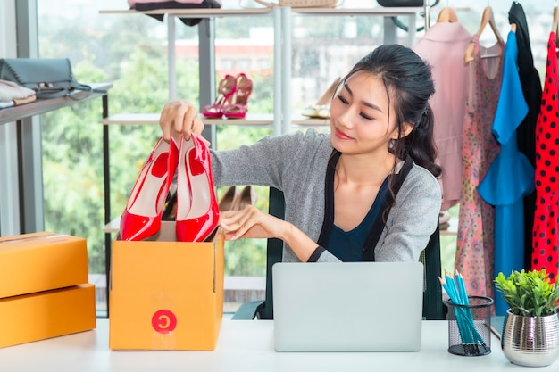 Glückliches asiatisches zufälliges damenarbeitsstart-kleinunternehmer kmu im kleidungsshop.