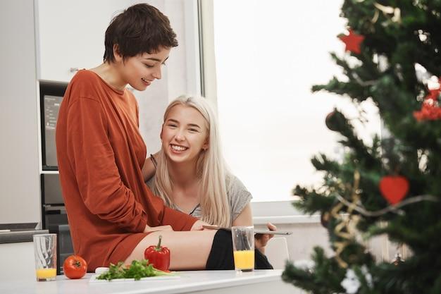 Glückliches attraktives blondes mädchen, das tablette hält und in die kamera lächelt, während sie neben ihrer schönen freundin in der küche nahe weihnachtsbaum sitzt. frauen lachen über artikel, die sie per gadget lesen.