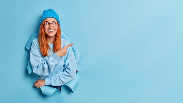 Glückliches attraktives junges mädchen lächelt breit hat langes rotes haar trägt blaues sweatshirt und hut.