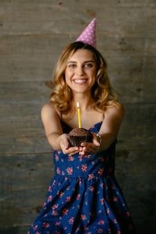 Glückliches attraktives mädchen hält einen schokoladenkleinen kuchen mit der kerze und feiert ihren geburtstag
