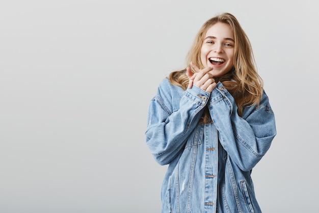 Glückliches attraktives mädchen klatschen in die hände und lächeln entzückt, erhalten eine unglaubliche überraschung