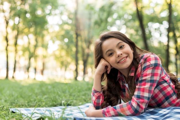 Glückliches attraktives mädchen, welches die kamera liegt im park betrachtet