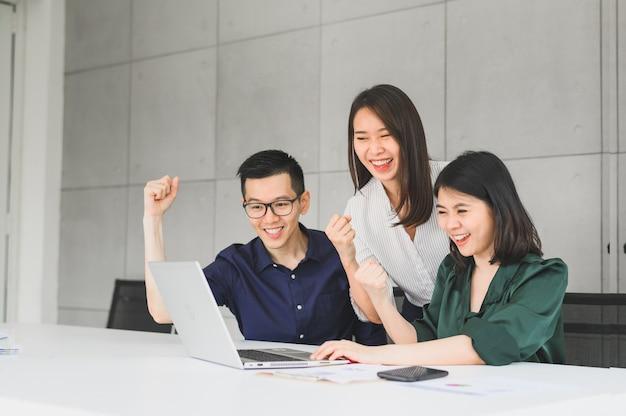 Glückliches aufgeregtes asiatisches geschäftsteam, das arm hebt, um erfolg zu feiern