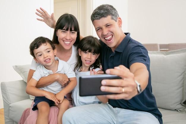 Glückliches aufgeregtes familienpaar, das entzückende kinder umarmt, zusammen auf der couch zu hause sitzt und selfie am telefon nimmt.