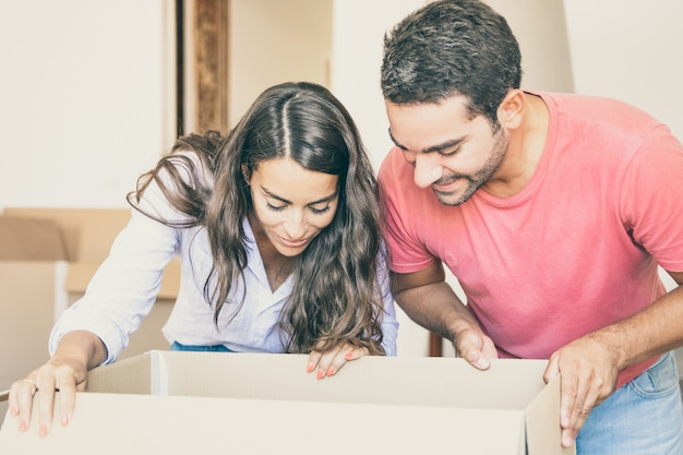 Glückliches aufgeregtes junges lateinisches paar, das karton öffnet und nach innen schaut, dinge bewegt und auspackt