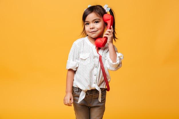Glückliches aufgeregtes kleines mädchen, das durch rotes retro- telefon spricht.