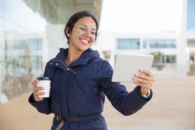 Glückliches aufgeregtes mädchen, das kaffee und videoanruf genießt