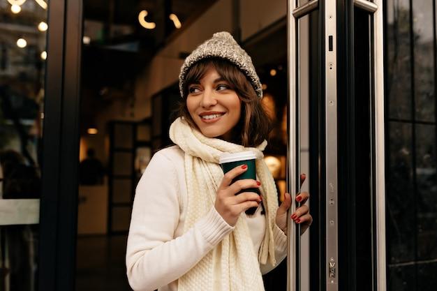 Glückliches aufgeregtes mädchen in den weißen gestrickten kleidern kam mit kaffee aus dem café heraus