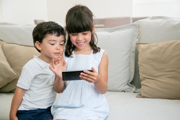 Glückliches aufgeregtes mädchen und ihr kleiner bruder spielen online-spiel am telefon, während sie auf der couch im wohnzimmer sitzen.
