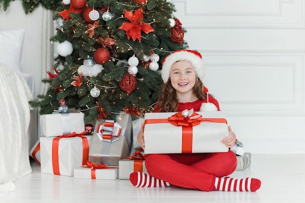 Glückliches aufgeregtes mädchenkind, das weihnachtsgeschenkbox hält.