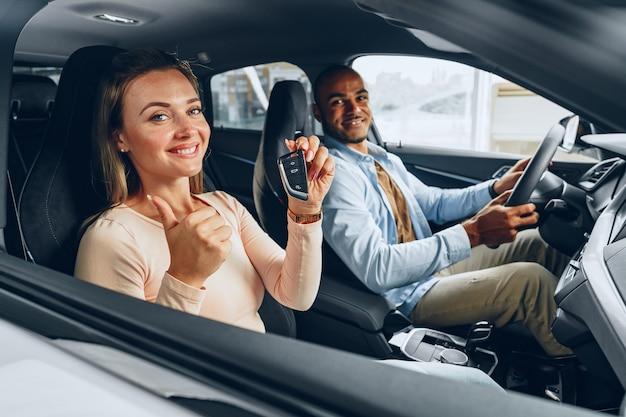 Glückliches aufgeregtes paar oder familie, die ein neues auto kauft und schlüssel zeigt
