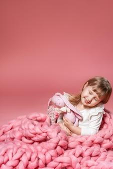 Glückliches baby auf dem rosa korallenhintergrund bedeckt mit decke und merino. mit freiem text platz.