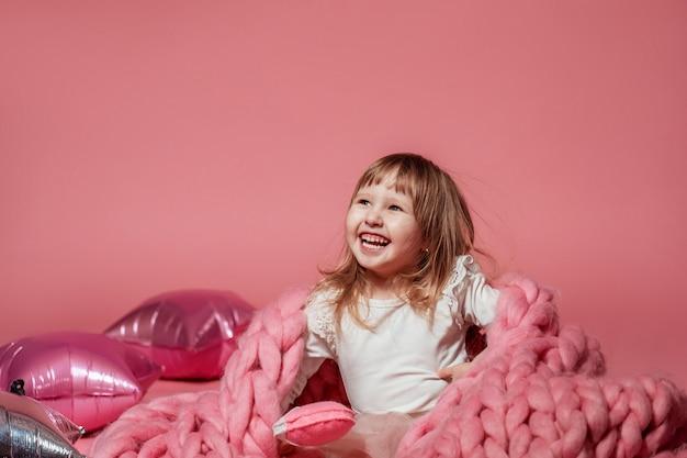 Glückliches baby auf dem rosa korallenhintergrund bedeckt mit decke und merino