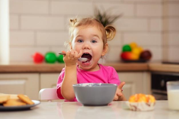 Glückliches baby, das am tisch in der küche sitzt und mit einem appetit isst