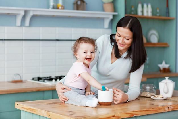 Glückliches baby, das auf dem küchentisch mit mutter sitzt, die brei mit einem löffel rührt