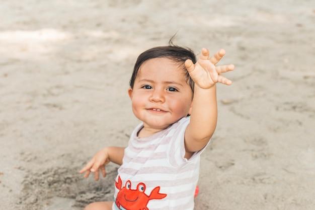 Glückliches baby, das auf sand sitzt
