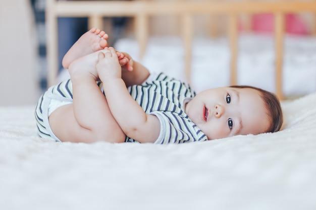 Glückliches baby, das auf weißem blatt liegt und ihre beine hält. spielerisches baby, das sich im bett hinlegt