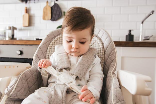 Glückliches baby, das im hochstuhl in einer weißen küche sitzt.