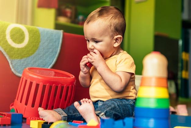 Glückliches baby, das im kindergarten mit bauklötzen spielt.