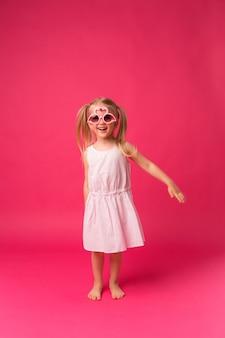 Glückliches baby, das in der sonnenbrille auf rosa hintergrund lächelt