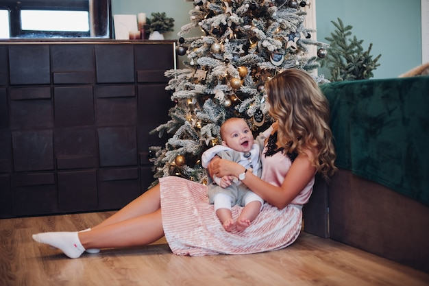 Glückliches baby, das in mutters armen neben geschmücktem weihnachtsbaum zu hause sitzt.