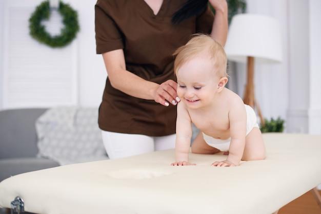 Glückliches baby, das massage mit professioneller masseurin hat. gesundheitswesen und medizinisches konzept. freundlicher und freundlicher kinderarzt.