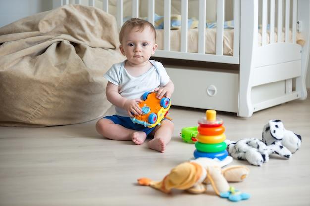Glückliches baby, das mit spielzeug auf dem boden im schlafzimmer spielt