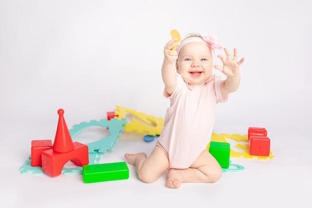 Glückliches baby, das mit würfeln auf weißem lokalisiertem hintergrund spielt, raum für text