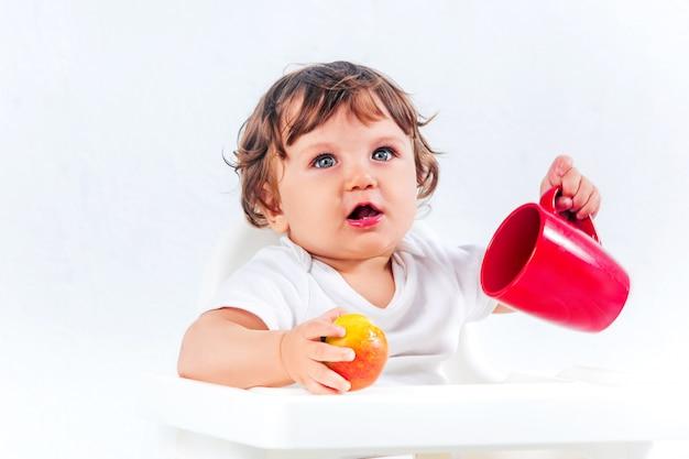 Glückliches baby, das sitzt und isst