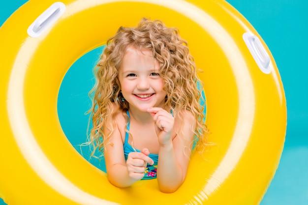 Glückliches baby im badeanzug mit dem kreis lokalisiert auf blauem hintergrund