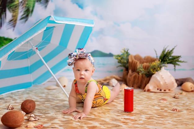 Glückliches baby in einem badeanzug nimmt ein sonnenbad auf einem sandstrand am meer unter einem sonnenschirm