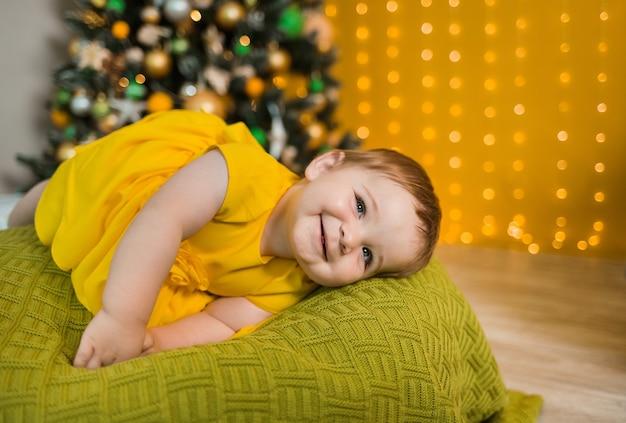 Glückliches baby in einem gelben kleid, das auf einem grünen kissen mit weihnachtsbaum liegt