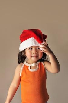 Glückliches baby in einem weihnachtskostüm santa claus auf hellbrauner farbwand.