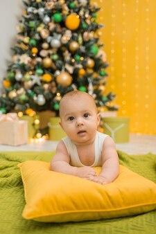 Glückliches baby in einem weißen body liegt auf einem kissen vor dem hintergrund eines weihnachtsbaumes. vertikale ausrichtung