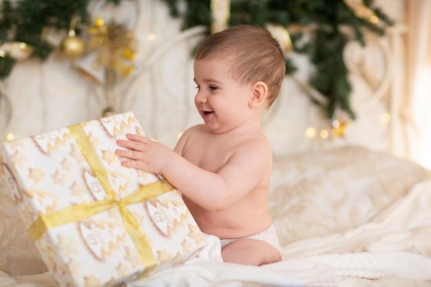Glückliches baby in einer weihnachtsmütze mit einem geschenk