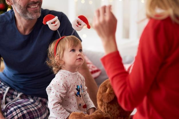 Glückliches baby mit den eltern am weihnachtsmorgen
